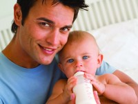 Father bottle feeding baby